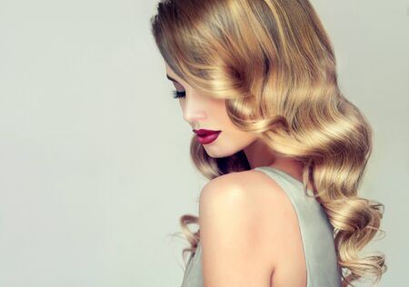 Young, blonde haired woman with elegant, voluminous evening hairstyle. Profile of woman framed by shiny curls of bonde hair. Reklamní fotografie