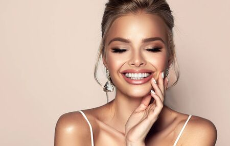 Portrait of beautiful woman with closed eyes and wide, happy toothy smile on the face. Splendid evening makeup, ripe lips painted in rose color and long black eyelashes.