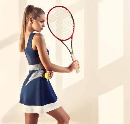 Well shaped, sporty woman with long ponytail hairstyle and trendy makeup is demonstrating attractiveness of physical activity. Sport, tennis, beauty and fashion.