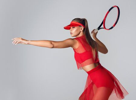 Gorgeous young woman dressed in sport outfit is holding tennis racket with readiness to beat back. Sport, tennis, beauty and fashion. Reklamní fotografie - 137529057