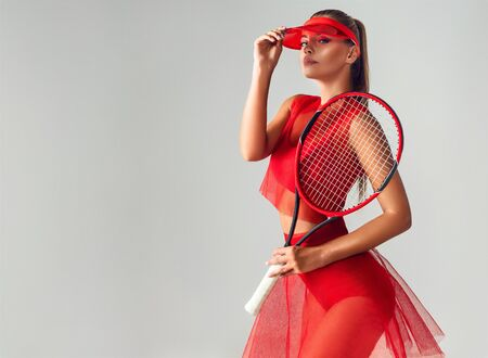 Gorgeous young woman dressed in sport outfit is holding tennis racket in the hand. Fitness, body sculpturing, sport games, tennis. Reklamní fotografie - 137529059