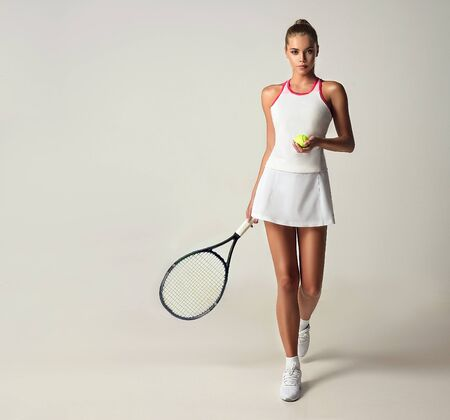 Model is holding tennis racket and ball in the hands and makes step forward. Dynamic movement. Sport and beauty. Reklamní fotografie - 137529061