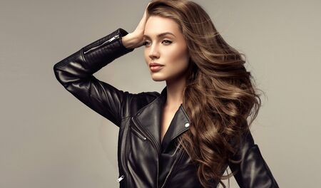 Portrait of attractive woman with long, dense, well groomed hair, dressed in trendy leather jacket. Hairdressing and modern trends. Reklamní fotografie - 137529063