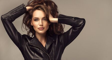 Bold look, elegant pose, bright makeup. Portrait of attractive woman with long, dense, well groomed hair, dressed in trendy leather jacket. Hairdressing and modern trends.