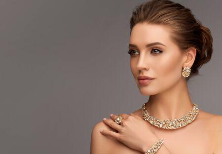 Mujer seductora vestida con un elegante conjunto de joyas de collar, anillo y aretes. Estilo de noche elegante.