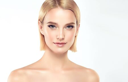 Gorgeous, young,woman with almond like eyes and fashionable hairstyle on the short blonde hair is touching tenderly the face. Facial treatment, cosmetology, beauty technologies and spa. Reklamní fotografie - 137529107