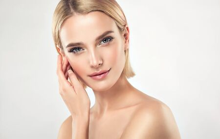 Gorgeous, young,woman with almond like eyes is touching tenderly the face. Facial treatment, cosmetology and spa.