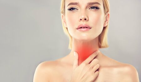 Young, attractive woman is touching the neck with expression of sharp pain on the face. Symbolic image of sore throat, any type of inflammation, endocrinology problems, thyroid gland diseases. Reklamní fotografie - 137529144