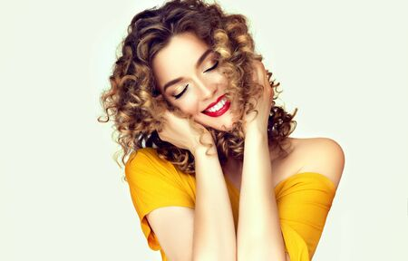 Young, beautiful woman with dense curly hairstyles and freckles on the cheeks is dreaming with closed eyes. Wide smile and feel of fun on facial expression of attractive model dressed in mustard color t-shirt. Фото со стока