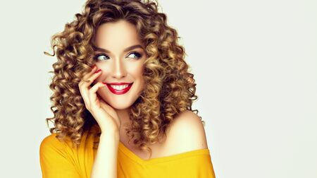 Beautiful woman with dense curly hair and freckles on the cheeks is happily looking aside. Look full of dreams and hopes.