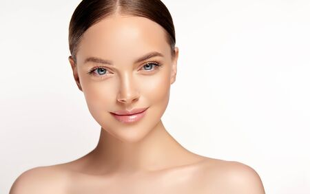 Penetrating look of blue-eyed young woman. Gorgeous, young, brown haired woman with clean fresh skin.Light smile on the perfect face. Facial treatment and cosmetology. Reklamní fotografie - 138689207