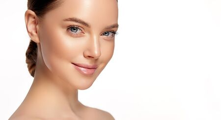 Portrait of perfectly looking young woman with pleasant facial expression and soft makeup.  Light smile on the beautiful face and elegant gesture. Facial treatment, cosmetology, beauty technologies and spa.