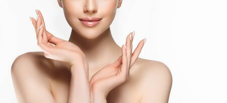 Bare shoulders, elegant gesture of hands and tender smile on the face. Human parts.  Makeup, cosmetology, cosmetic procedures and products. Stock Photo