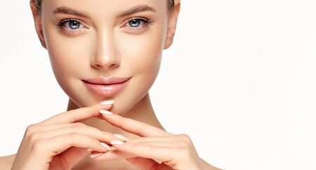 Penetrating look of blue-eyed young woman. Gorgeous, young, brown haired woman with clean fresh skin. Light smile on the perfect face  with pleasant expression. Facial treatment, cosmetology, beauty technologies and spa. Stock Photo
