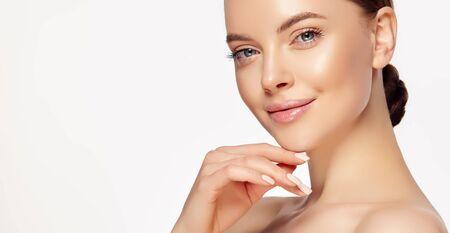 Porträt einer perfekt aussehenden jungen Frau mit angenehmem Gesichtsausdruck und weichem Make-up. Leichtes Lächeln auf dem schönen Gesicht und der eleganten Geste. Gesichtsbehandlung, Kosmetik, Schönheitstechnologien und Spa.