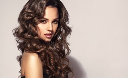 Bold and dazzling look of beautiful lady. Model with long, curly, well groomed hair. Excellent hair waves. Hairdressing art and hair care.