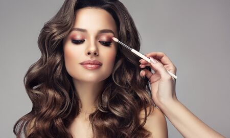 Hand of makeup artist is coloring eyelid of lovely model.  Light smile on the beautiful face of woman with long, dense, curly hairstyle and vivid makeup. Makeup, hair care and hairdressing art. Reklamní fotografie - 141243922