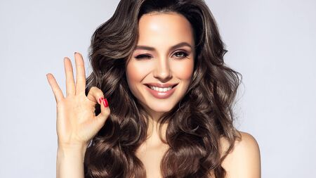 Young, brown haired woman  with voluminous hairstyle is showing sign of success, wide toothy smile on her face.  Hairdressing art, hair care and beauty products.