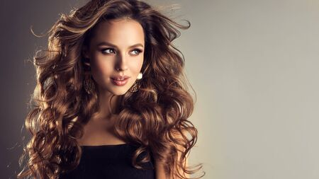 Flying hair, pretty smile and emotional look. Beautiful model with long, dense, curly hairstyle and vivid makeup. Bold and dazzling look of beautiful lady.