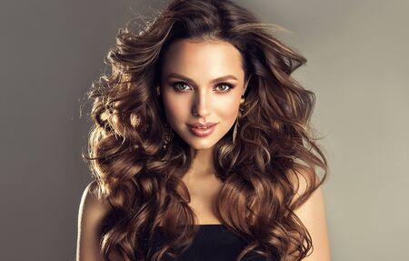 Beautiful model with long, dense, curly hairstyle and vivid makeup. Bold and dazzling look of beautiful lady. Hairdressing art, hair care and beauty products. Foto de archivo