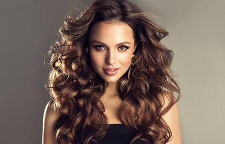 Schönes Modell mit langer, dichter, lockiger Frisur und lebendigem Make-up. Kühnes und schillerndes Aussehen einer schönen Dame. Friseurkunst, Haarpflege und Schönheitsprodukte. Standard-Bild