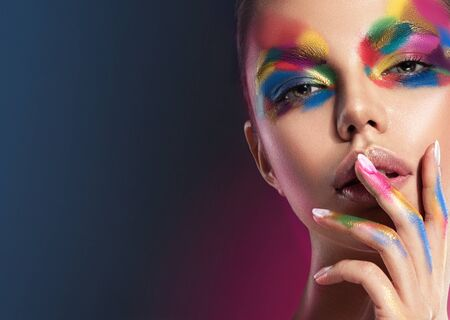 Bright, extravagant, multi colored makeup on the young pretty face. Makeup art, manicure and cosmetic products. Reklamní fotografie - 141243913