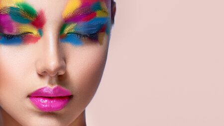 Close-up detail of woman face with closed eyes covered by palette of tints. Artistic makeup and cosmetic products. Reklamní fotografie - 141243914