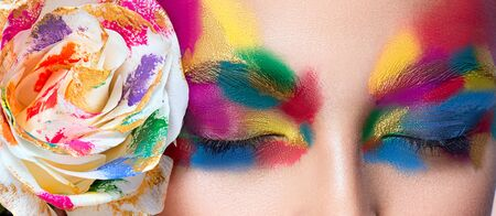 Closed eyes shaded in a  various colors. Paletted rose is touching the face of model. Beauty and sensuality.  Artistic makeup and cosmetic products.