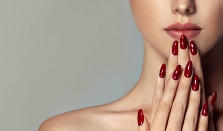 Perfect manicure red in front of pale rose lips. Make up, nail care and cosmetic products. Reklamní fotografie