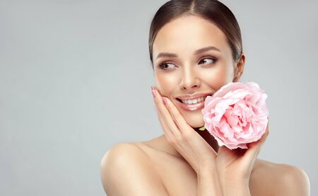 Gorgeous, young woman is holding big pale-rose flower with gentle smile.  Natural facial treatment, cosmetology, beauty technologies and spa.