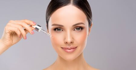 Gorgeous, young woman with clean, fresh skin. Small, clean drop on the cheek of gorgeous young woman. Facial treatment.