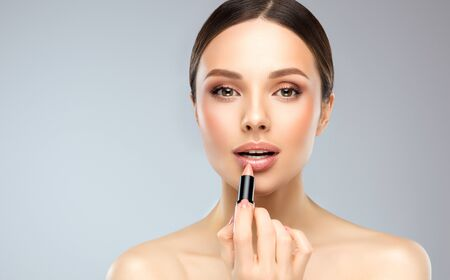 Beautiful woman with bare shoulders is coloring lips in a pale rose shade. Soft, kind look and  accurate gesture. Female beauty. Natural facial treatment, make up, beauty technologies and spa. Reklamní fotografie - 144105967