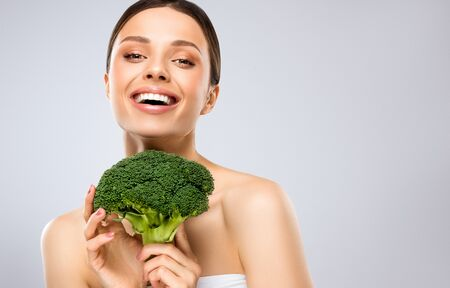 Model with the vegetable. Laughing young woman is holding fresh, green broccoli in the hands. Toothy smile and shiny facial expression. Healthy, vegetarian meal as a cause of beauty. Vegetables, beauty and happiness. Reklamní fotografie - 144105969