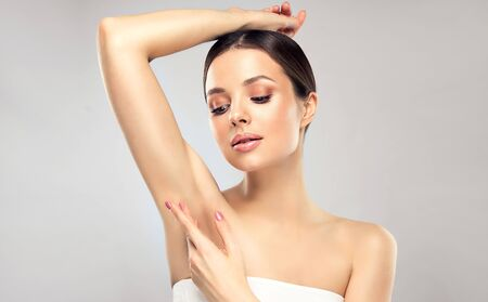 Beautiful, young, brown haired woman with clean fresh skin is touching armpit by gentle gesture. Expression of calmness on the perfect face. Body treatment, cosmetology, beauty technologies and spa. Reklamní fotografie - 144105972