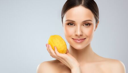 Gorgeous, young woman is holding a big yellow lemon with gentle smile. Soft, kind look and tender smile as symbol of human vitality. Natural beauty and vegetarian attitude. Reklamní fotografie - 144105973