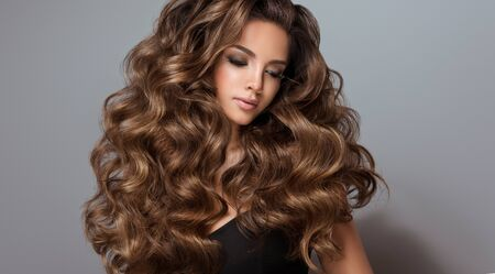 Young, brown haired beautiful model with long,  curly, well groomed hair. Excellent hair waves. Hairdressing art and hair care. Reklamní fotografie