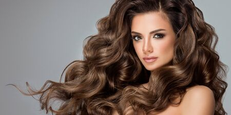 Model with bright makeup on the face is demonstrating frizzy and dense hairstyle. Hairdressing art, hair care and beauty products for hair care.