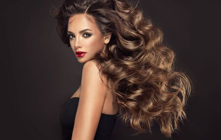 Young, brown haired beautiful model with long,  curly, well groomed hair. Excellent hair waves. Hairdressing art and hair care. Reklamní fotografie - 148711163