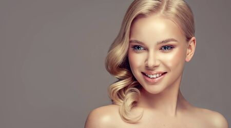 Portrait of beautifully looking young blonde haired woman, dressed in a delicate evening makeup.Perfect model with wide, toothy smile on the face. Beauty, elegance, hairstyling, cosmetic and dentistry. Reklamní fotografie - 148711164