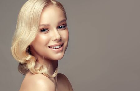 Perfect model with wide, toothy smile on the face is looking at the viewers with tenderness. Beauty, elegance, hairstyling, cosmetic and dentistry.