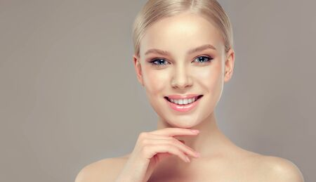 Gorgeous, young, blond haired woman with neat and delicate makeup on the face is touching own chin by elegant gesture. Wide, toothy smile on the perfect face. Facial treatment, cosmetology, beauty technologies and spa. Reklamní fotografie - 148711168
