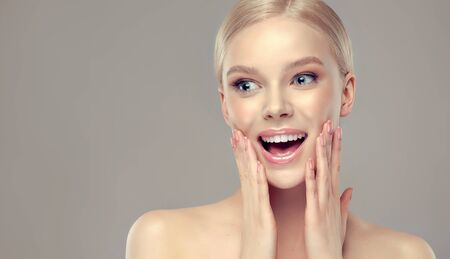 Portrait of loudly screaming young model.  Beautiful woman is touching the face by both hands and looking aside with the feel of surprise and happiness. Look full of fun and joy. Entertainment and advertisement.