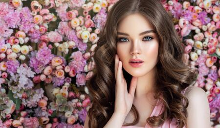 Portrait of perfectly looking young woman dressed in splendid evening makeup. Well shaped lips, painted in rose color, long black eyelashes above almond like,misty eyes and tender look at viewers.  Portrait on the floral background.