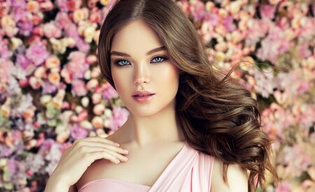 Portrait of perfectly looking young woman dressed in splendid evening makeup. Well shaped lips, painted in rose color, long black eyelashes above almond like,misty eyes and tender look at viewers.  Portrait on the floral background. Reklamní fotografie - 150001723