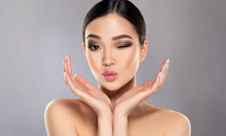 Black haired young woman with asian appearance is demonstrating dense, well cared, straight hair and vivid evening makeup on the face.Oriental beauty. Hairdressing art, hair care and beauty products.