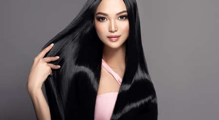 Black haired young woman with asian appearance is demonstrating dense, well cared, straight hair and vivid evening makeup on the face.Oriental beauty. Hairdressing art, hair care and beauty products. Reklamní fotografie - 151419421