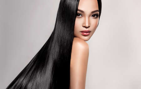 Black haired young woman with asian appearance is demonstrating dense, well cared, straight hair and vivid evening makeup on the face.Oriental beauty. Hairdressing art, hair care and beauty products. Reklamní fotografie - 151419424