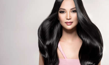 Black haired young woman with asian appearance is demonstrating dense, well cared, straight hair and vivid evening makeup on the face.Oriental beauty. Hairdressing art, hair care and beauty products. Reklamní fotografie - 151301960