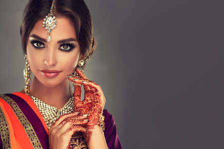 Black haired indian young woman dressed in a traditional, costume-sari. Attractive hairstyle, splendid makeup,henna-tattoos on the hands and local indian style jewelry. Oriental beauty.
