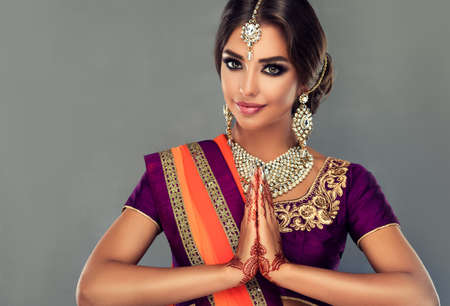 Attractive Indian woman is demonstrating welcome gesture-namaste. Portrait of beautiful indian girl dressed in a traditional national suit, mehndi henna tattoo is painted on her hands.Oriental beauty. Reklamní fotografie - 152316320
